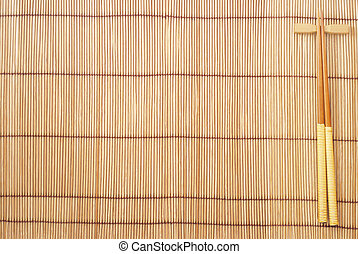 Chopsticks on brown bamboo matting background