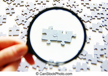 magnifying glass - Hand with magnifying glass and puzzle...