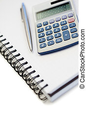 Angled notebook with pencil and pocket calculator on a white...