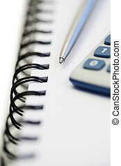 Spiral notebook with pencil and pocket calculator on a white...