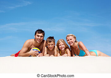 Weekend - Photo of happy family lying on sand on summer...