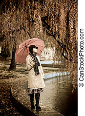 Girl in cloak and scarf with umbrella at park in rainy day...