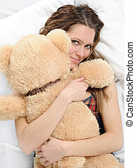 Young woman with teddybear - Young woman on a bed in an...