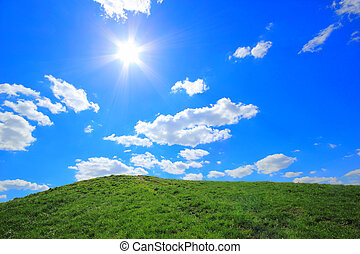 Green grass hills under midday sun in blue sky.