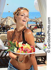 Young smiling woman with fruits salad by the sea