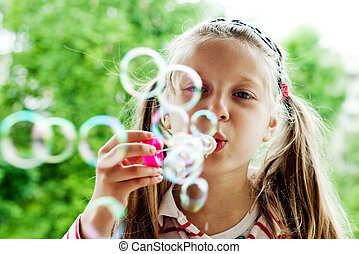 Leisure - An image of a nice little girl blowing bubbles