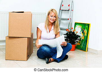 Woman in the new apartment - Woman with cardboard boxes on...