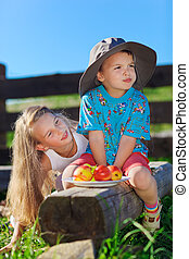 Cute blond little girl and boy in funny hat playing with...