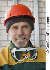 An elderly worker with spectacles and a protective helmet