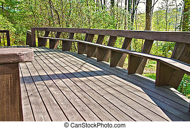 Wood Deck Design with Bench - A wooden deck on a house with...