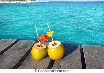 coconut coktails in caribbean on wood pier