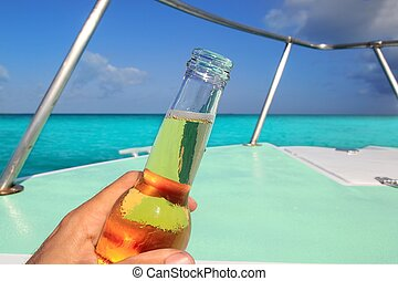 beer on hand Caribbean in boat bow turquoise sea enjoying...