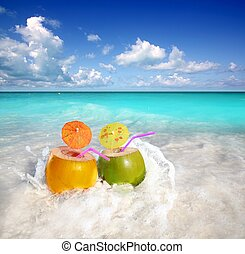 coconut cocktails juice in tropical beach water splash...