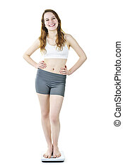 Healthy young girl standing on bathroom scale