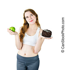 Young girl holding apple and cake - Tempted young woman...