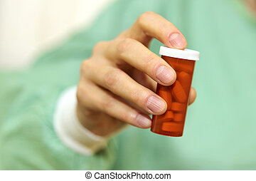 doctor holding bottle of prescription pills