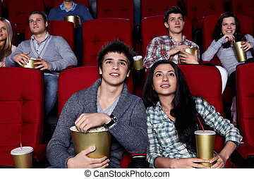Cinema - Young people are closely watching a movie at the...
