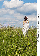 Rural scene. Day summer time. Back of the woman in a white...