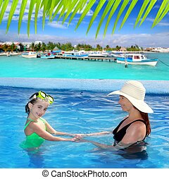 daughter and mother in swimming pool tropical location...