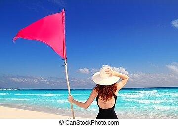 beach rear woman holding red beach flag pole