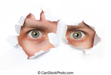 Eyes looking through a hole in a paper isolated