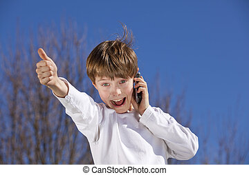 boy with a cell phone posing thumbs