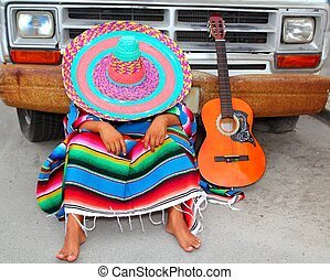 Lazy nap mexican guy sleeping on grunge car with guitar and...