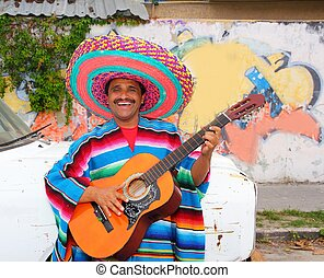 Mexican humor man smiling playing guitar sombrero poncho in...