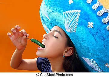 Mexican girl profile eating jalapeno hot chili pepper...