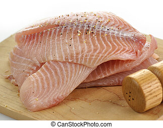 tilapia fillets on a cutting board with spices