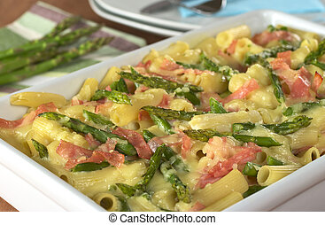 Casserole of green asparagus, ham and macaroni with raw green asparagus and plates in the back (Selective Focus, Focus one third into the dish)