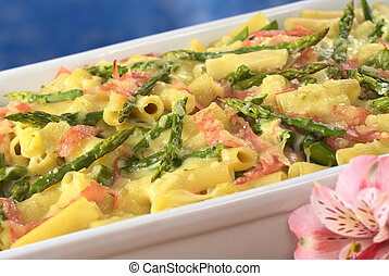 Green asparagus-ham-macaroni casserole with grated cheese on top and a pink Inca Lily in front (Selective Focus, Focus one third into the dish)