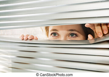Woman - An image of a woman looking through the blinds