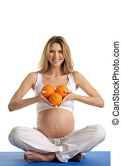 Pregnant woman practicing yoga with oranges isolated on...
