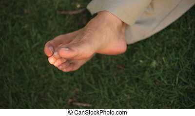 A man\'s feet on the grass in the park