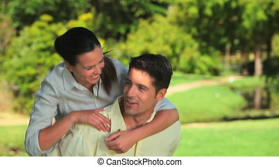 Man giving a piggy back to his wife