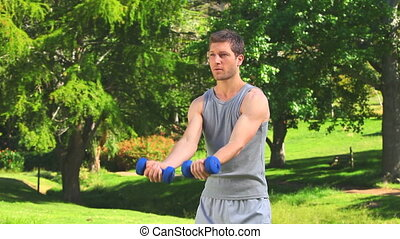 Young man doing exercise outdoors in a park