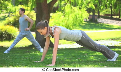 Couple doing musculation exercises in a park