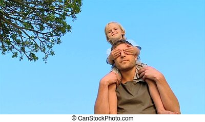 Dad holding son on his shoulders in the park