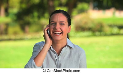 Cute woman on her mobile phone - Cute woman laughing and...
