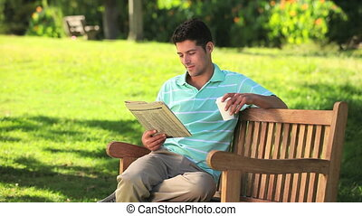 Man reading a newspaper while drinking a coffee on a park...