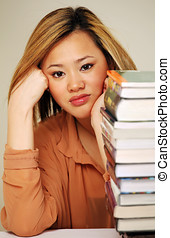 Pretty chinese student with pile of books