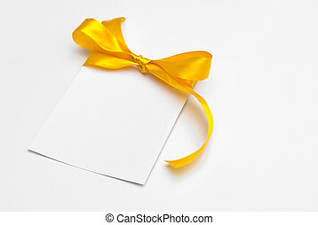 Blank gift tag tied with a bow of yellow satin ribbon