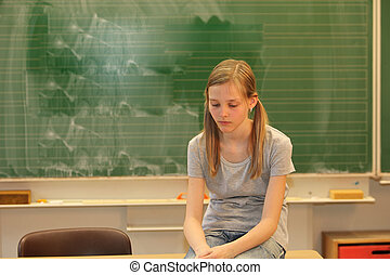 Sad blonde girl in school in front of a blackboard with his...
