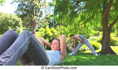 Athletic couple excercising outdoor - Woman doing sit-up...