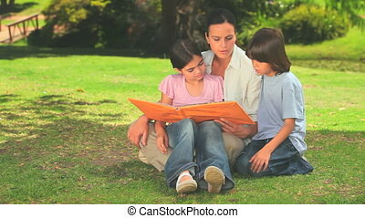 Mother reading to her children while sitting on the grass in...