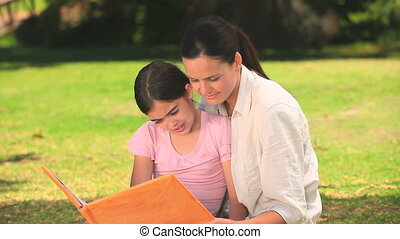 Mother reading to her daughter while they sit on the grass...