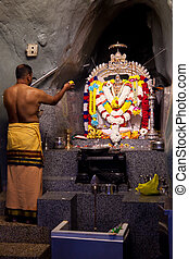 Hindu man praying at an alter in the Batu caves