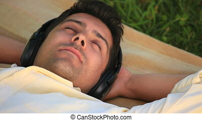 Man lying listening to music - Man lying outdoors on a rug...