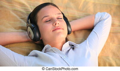 Relaxed woman listening to music - Woman lying relaxing...
